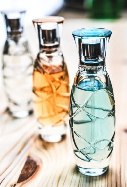 Three perfume bottles are in diagonally lined up on a wooden table. The blue one is closest to the camera, then there is an amber one, and then a clear one