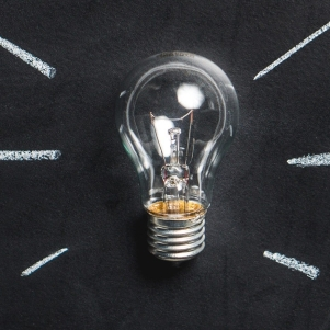 A lightbulb sits on a chalkboard background with white lines coming from it