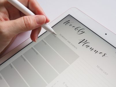 A man has a tablet with a weekly planner on the screen. She is holding a stylus to enter data
