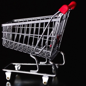 A shopping cart with a red handle sits on a black tabletop