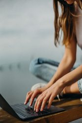 A young woman sits on a bench and is typing on a black laptop