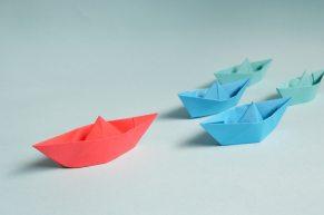 Paper boats on a surface. There is a large red one, two smaller blue ones behind it and then 2 smaller teal ones behind those.