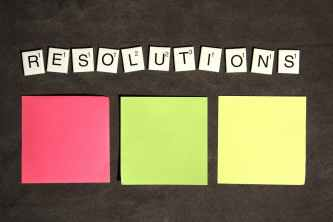 """""""Resolutions"""" is spelled out in scrabble letters with a red, green and yellow sticky note below it. All sitting a couch cushion"""