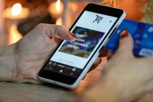 A shopping screen on a smartphone is held in a woman's hand. She has a credit card on the other hand