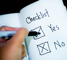 On white paper there is a title saying Checklist. Below are options reading Yes or No with a checkmark in the yes box and an x in the no box. A person holds a sharpie over the list,