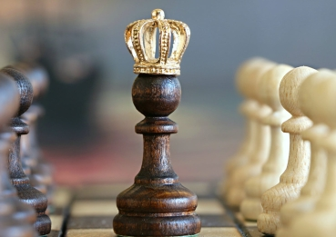A pawn sits in the middle of a chessboard with a crown on it. Other pawns of white and brown are on either side.