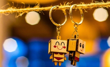 Two happy robot keychains hanging from a piece of string