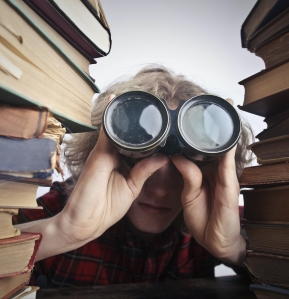 Person searching with binoculars in between two stacks of books