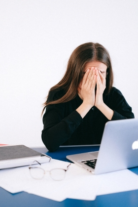 A stressed woman in front of her computer with her hands over her face