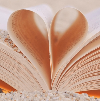 An open book with its centre pages curled together to form a heart. The book sits in a pile of pebbles and sand, and there is sand on one of the pages too.