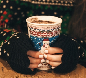 Girl in a Christmas sweater with a holiday-themed mug of hot chocolate in her hands.