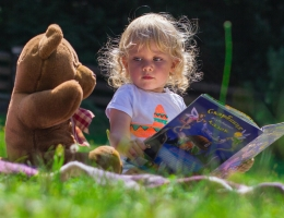 Little girl reading a book to her teddy bear on a picnic blanket on grass
