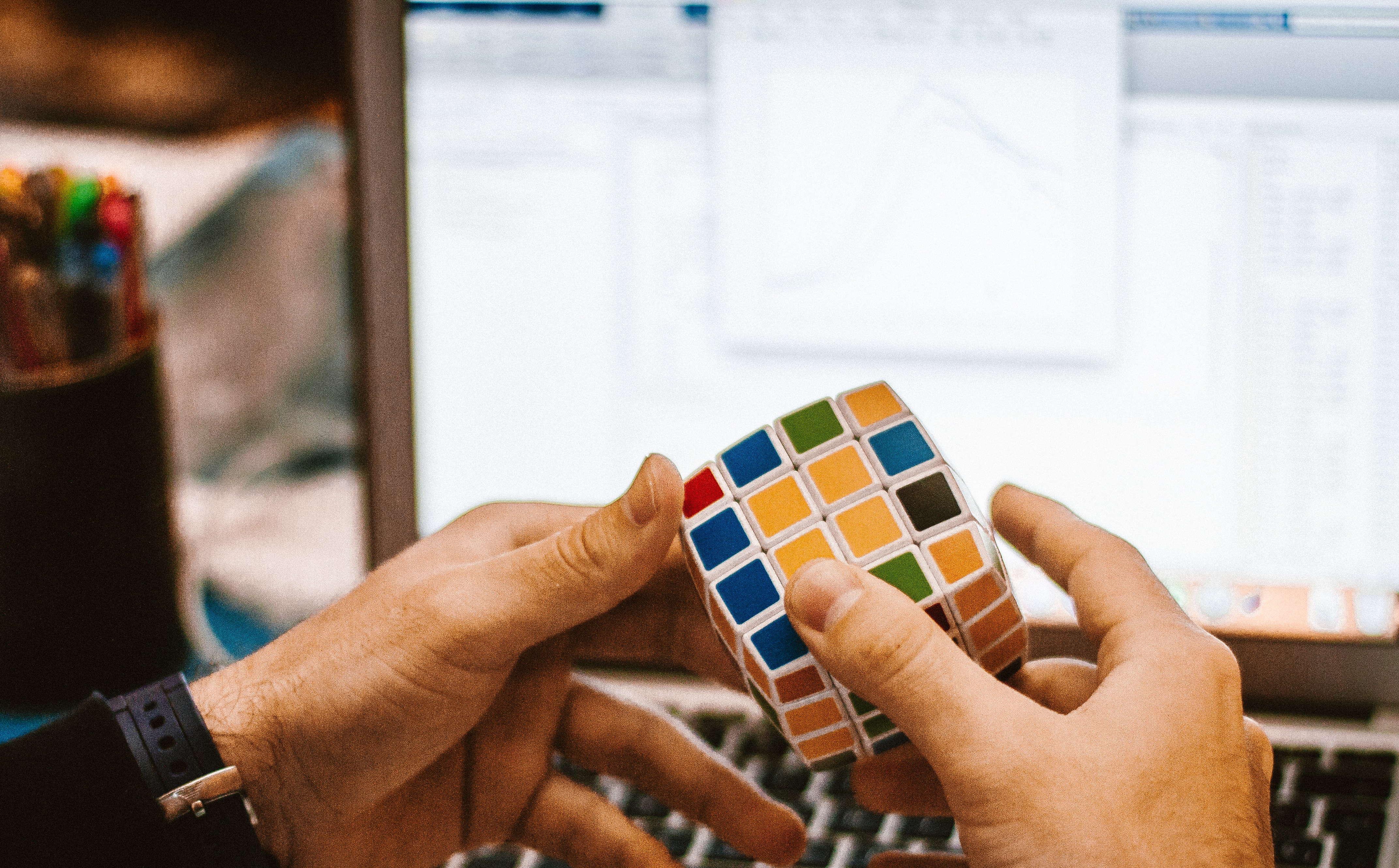 Man playing with a rubiks cube in front of a computer at a desk.