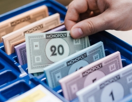 Bank from Monopoly. A hand grabs one of the neatly organized 20-dollar bills