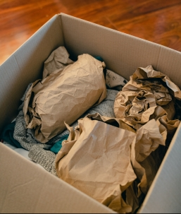 Moving box with paper-wrapped breakables and a sweater in it.