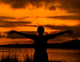 Triumphant woman silhouetted against an orange and vivid sunset