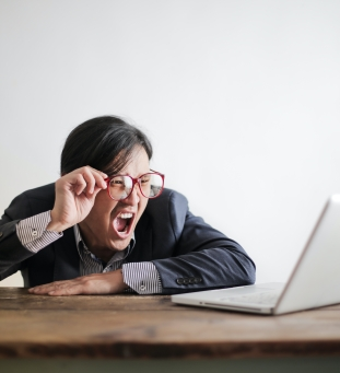 Angry and offended person yelling at laptop on the table.
